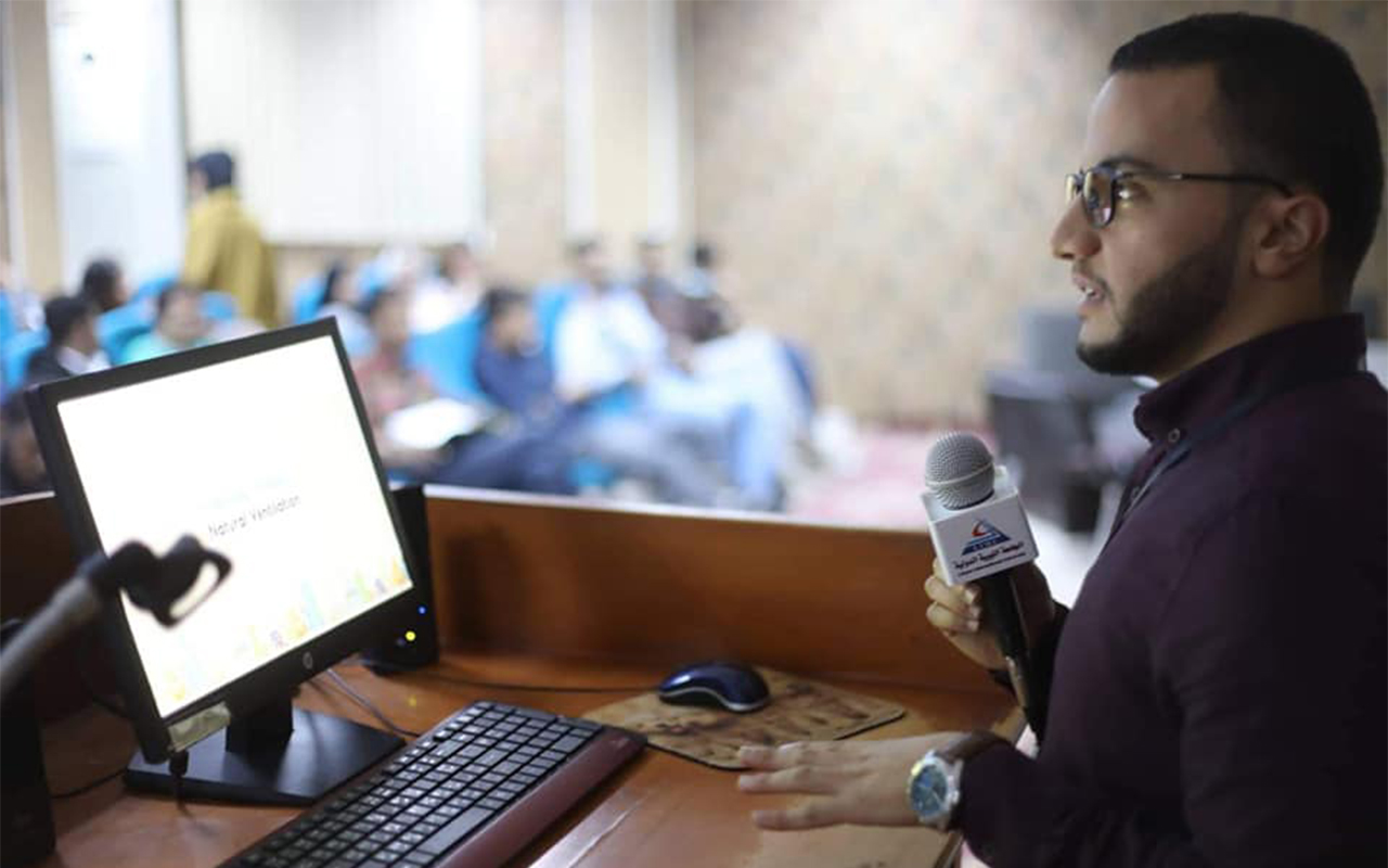 Gamaleldin Tarakhan at podium with microphone and computer talking to people.