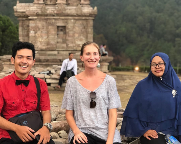 Devon Jancin sided by two local participants in front of a monument in Java.
