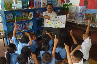 Mario García showing a workbook to children in classroom.