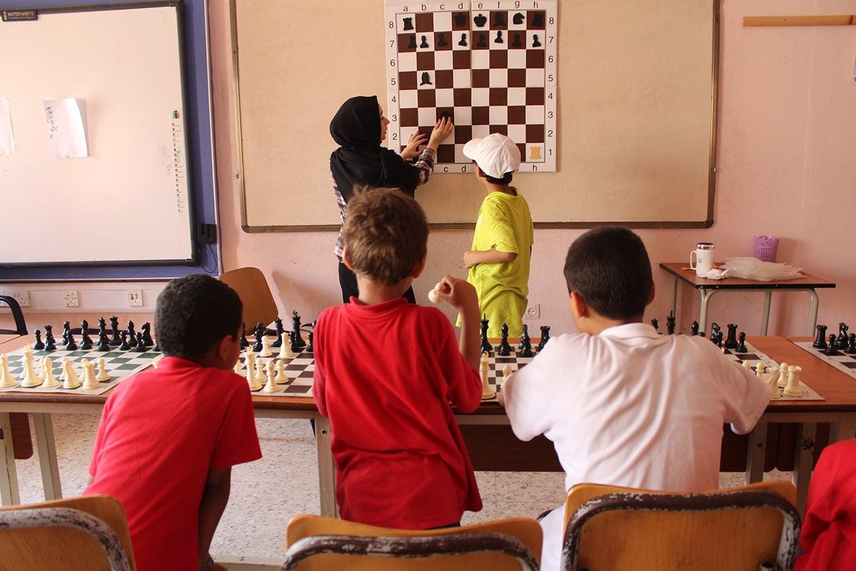 Ekram Aljadidi with children in a classroom.