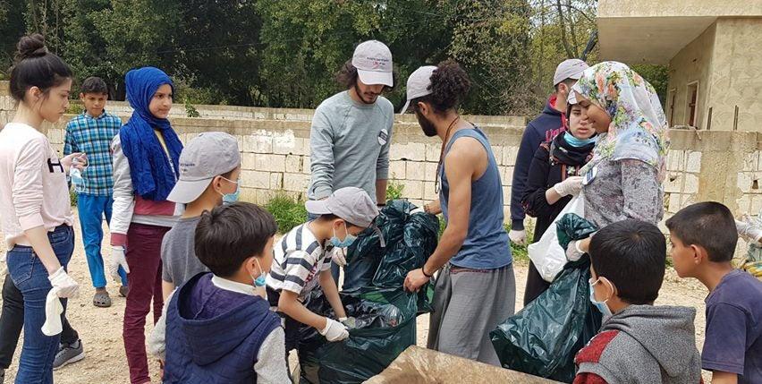 Razan Amani with volunteers cleaning up trash.