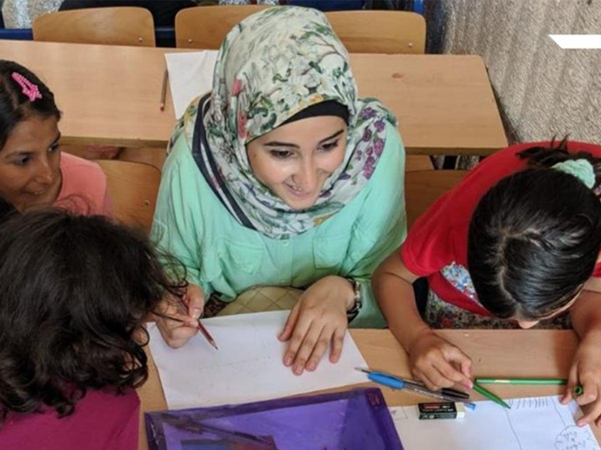 Razan Amine helping children with reading skills.