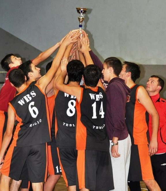 Basketball youth players huddled together raising a trophy.