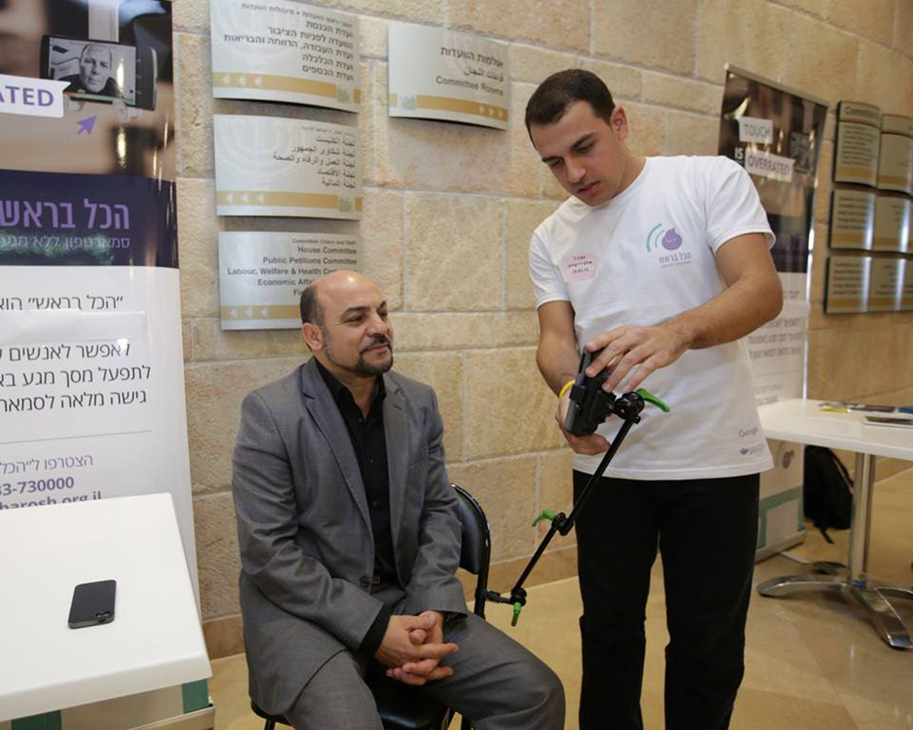 Khaled Ghanayem showing an artificial limb to a person.