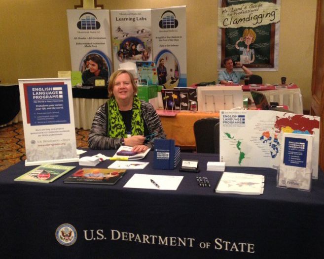 English Language Fellow at a stand in a TESOL conference displaying ELF program materials.