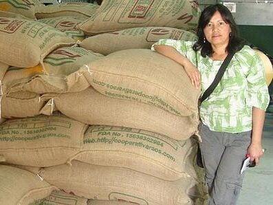 Mayra Orellana-Powell standing next to piles of big shipping coffee bags.