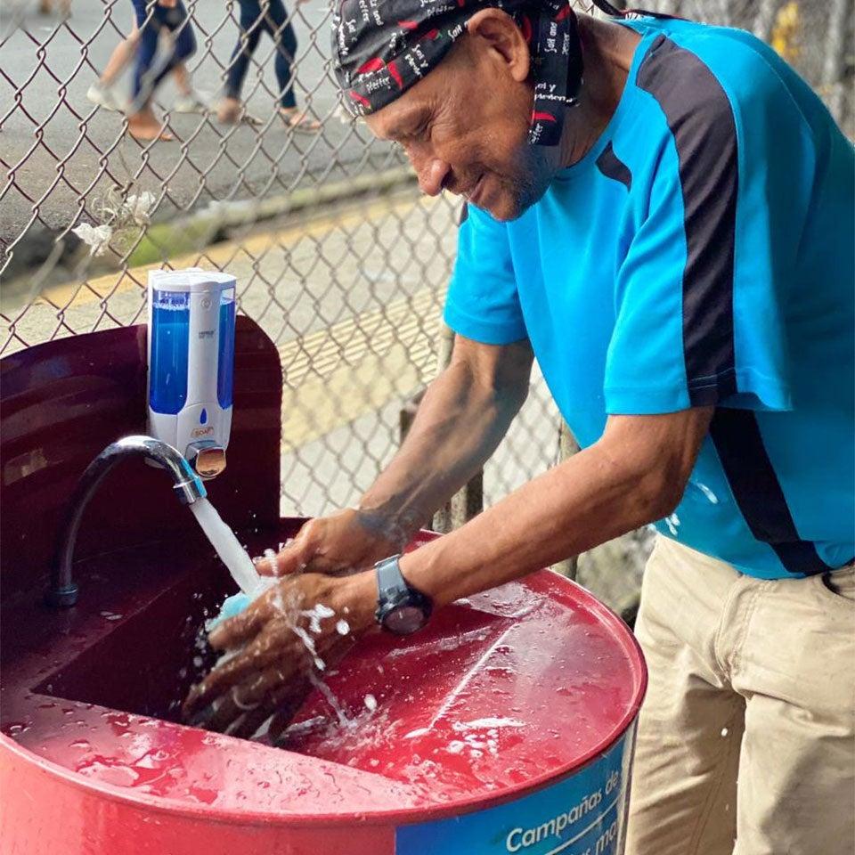 Man washing his hands in a handwashing station
